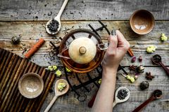 Brouw thee met bloemen en kruiden Giet de thee De theepot van de handgreep op houten hoogste mening als achtergrond stock fotografie