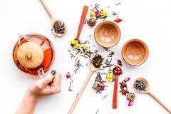 Brouw thee met bloemen en kruiden Giet de thee De theepot van de handgreep op witte hoogste mening als achtergrond royalty-vrije stock foto's