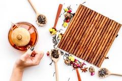 Brouw thee met bloemen en kruiden Giet de thee De theepot van de handgreep op witte hoogste mening als achtergrond royalty-vrije stock afbeelding