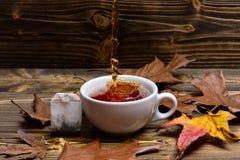 Brouwend theeconcept Kop het gieten met water of thee met plonsen op donkere houten achtergrond Kop, de herfstbladeren en Royalty-vrije Stock Foto