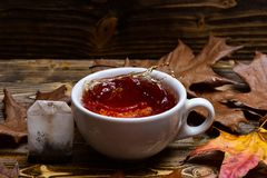 Brouwend theeconcept Kop het gieten met water of thee met plonsen op donkere houten achtergrond Mok het gieten met vloeistof met Stock Foto