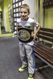 Brovary L'Ucraina, 14 11 2015 che un ragazzino sorridente sta provando su una cinghia di pugilato del campione fotografia stock libera da diritti