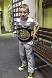 Brovary. Ukraine, 14.11.2015 a smiling little boy is trying on a champion boxing belt royalty free stock photography