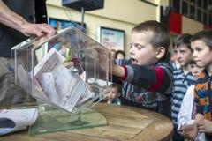Brovary ukraine Vermaakcentrum 25 04 2015 De jongen draait een doos met loterijkaartjes stock foto's