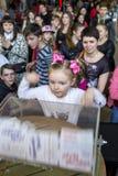 Brovary ukraine Vermaakcentrum 25 04 2015 Een klein meisje staart bij de het draaien doos met loterijkaartjes stock foto