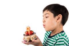 Browing Kerze des kleinen Jungen auf dem Kuchen für seinen Geburtstag Stockbild