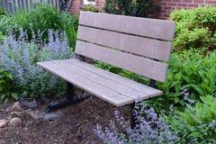 Brown ławka otaczająca kwiatami Obraz Stock