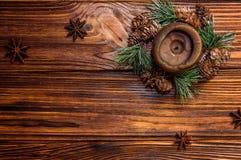Brown świeczka dekorująca z jedlinową gałąź z małymi rożkami Gwiazdkowate anyżowe owoc lokalizują w pobliżu zdjęcia stock