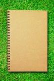 Brown-Abdeckungnotizbuch auf Feld des grünen Grases Stockfotografie