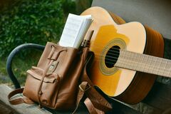 Brown Acoustic Guitar Beside Brown Leather Bucket Backpack on Brown Wooden Bench Royalty Free Stock Image