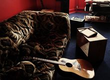 Brown Acoustic Guitar Leaning on Brown Velvet Couch royalty free stock image