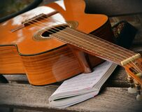 Brown Acoustic Guitar on White Music Note Book Stock Image