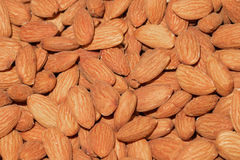 Brown almond background. Peeled almonds closeup. Brown background stock images