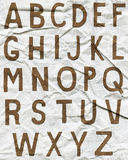 Brown-Alphabetbuchstaben auf zerknittertem Papier Stockbild