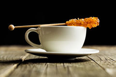 Brown amber sugar crystal on wooden stick and coffee cup. Stock Photos