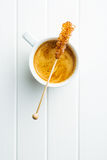 Brown amber sugar crystal on wooden stick and coffee cup. Royalty Free Stock Photography