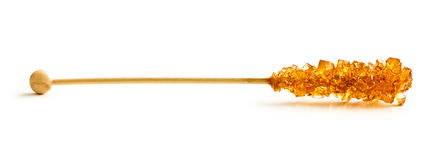 Brown amber sugar crystal on wooden stick. Royalty Free Stock Photos