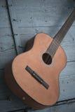 Brown antykwarska gitara na błękitnym drewnianym drzwiowym tle Zdjęcia Royalty Free