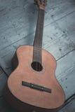 Brown antykwarska gitara na błękitnym drewnianym drzwiowym tle Obraz Royalty Free