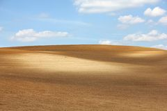 Brown arable hill against blue sky. Colorful brown arable hill against cloudy blue sky Royalty Free Stock Photo