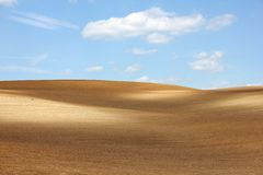 Brown arable hills against blue sky. Colorful brown arable hills against cloudy blue sky Royalty Free Stock Photo