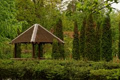 Brown arbor among the vegetation in the theme park. Green vegetation and wooden structure in the park Royalty Free Stock Image