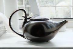 Brown asian teapot on the white windowsill Stock Photo