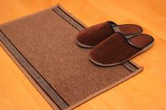 Brown autoguident des pantoufles sur le plan rapproché de tapis de plancher Photo stock