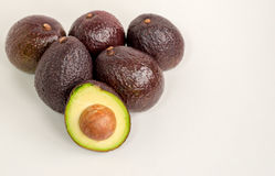 Brown avocado isolated with green half with seed white background Royalty Free Stock Photos