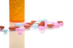 Brown, azul, e comprimidos da cor-de-rosa com frasco Fotografia de Stock Royalty Free