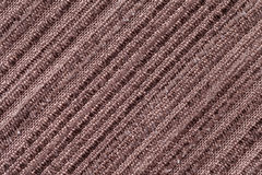 Brown background of a knitted textile material. Fabric with a striped texture closeup. Royalty Free Stock Images
