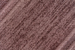 Brown background of a knitted textile material. Fabric with a striped texture closeup. Royalty Free Stock Image