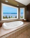 Brown-Badezimmer mit neuer Wanne- und Wasseransicht. Stockbild