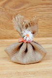 Brown bag closed with a ribbon and a flower Stock Photos