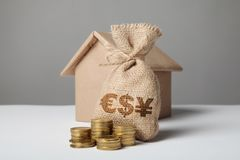 Brown bag with logo of dollar, euro and yuan. Gold coins and homemade paper house. Concept renting and buying home, property taxes stock photography
