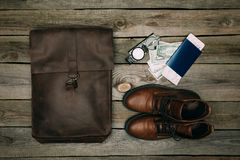 Brown bag and shoes with passport and money. Flat lay of brown bag and shoes, passport and money with a compass on a wooden surface. journey concept Royalty Free Stock Photography
