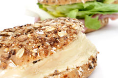 Brown bagel filled with cheese spread Royalty Free Stock Photos