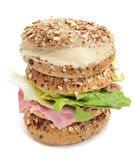 Brown bagels filled with spreadable cheese and ham and lettuce m. Two brown bagels topped with different seeds, such as sesame and poppy seeds, one filled with Stock Image