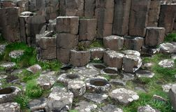 Brown basaltic columns, green grass and water in Ireland. Brown basaltic columns, green grass, water and tops of basaltic prisms fragment of the Giant's Royalty Free Stock Photography