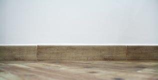Brown baseboard under a white wall Stock Photos