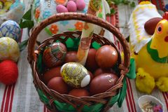 At Easter in the basket there are many red eggs. The brown basket is on the table.There are other items beside the basket Royalty Free Stock Photo