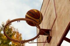 Brown Basketball Above Steel Basketball Hoop stock photography
