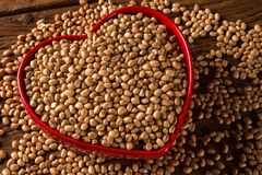 Brown beans in heart bowl on wooden background