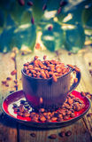 Brown beans pouring coffee cup Royalty Free Stock Photos