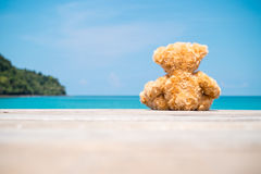 Brown bear doll sit on wooden floor at the sea Stock Photos