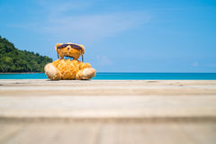 Brown bear doll sit on wooden floor at the sea Royalty Free Stock Photography