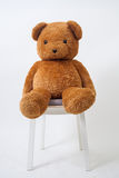 Brown bear doll siting on wood chair Royalty Free Stock Photos