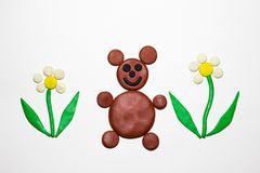 Brown bear among the flowers are made of plasticine. The bear is a forest animal. stock photography