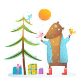 Brown bear wearing warm winter coat with birds friends celebrating Christmas. Stock Images