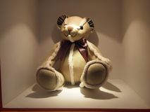 Brown bear and white lace bear doll, sitting quietly on the display stand, the light shining on the bear stock image